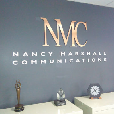 Raised logo in metallic brushed finish for Nancy Marshall Communication's reception counter in her Augusta offices
