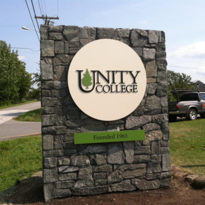 This sign for Unity College features raised letters, is 100% recyclable aluminum, and was installed to their existing stone structure.