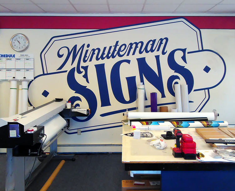 Minuteman Signs supergraphic logo on the shop's wall